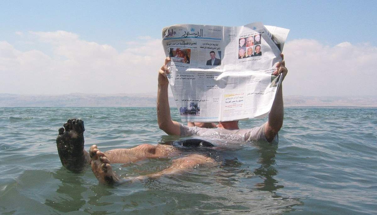 Reading newspaper in the Dead Sea
