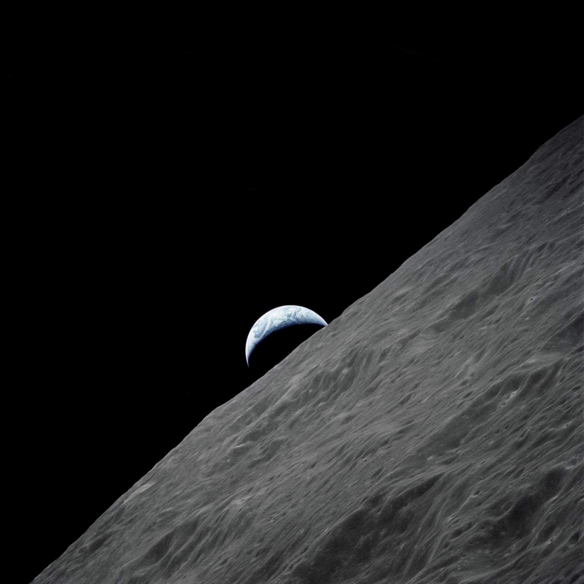 Crescent Earth rises above the lunar horizon - Apollo 17 photo