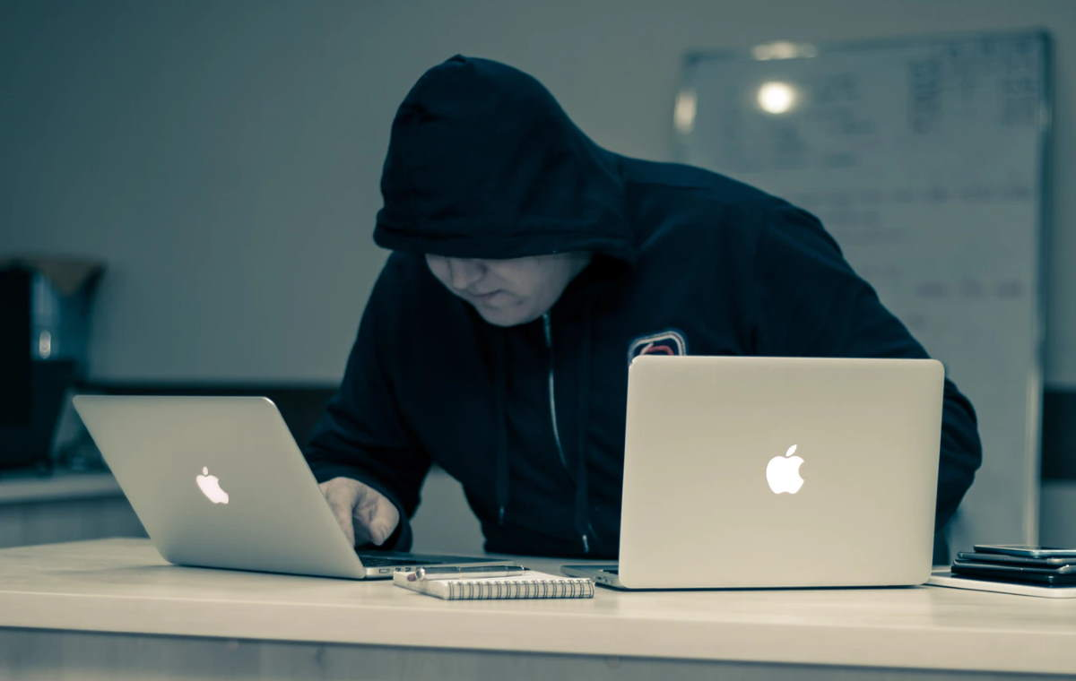 Man in black using two notebook computers