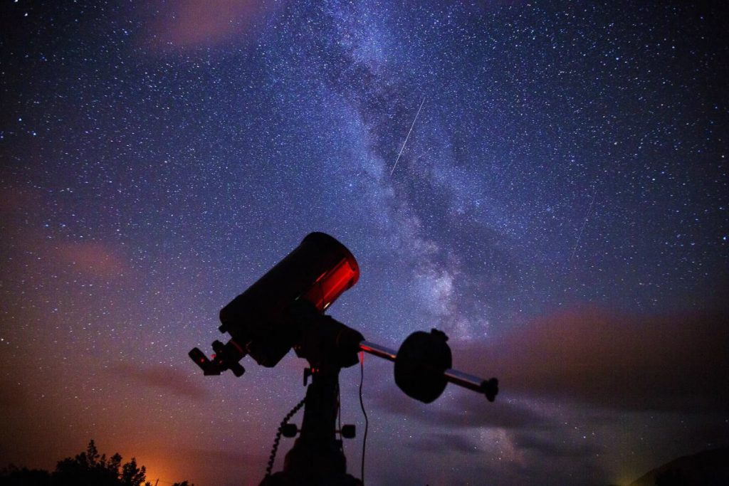 Telescope and starry night sky