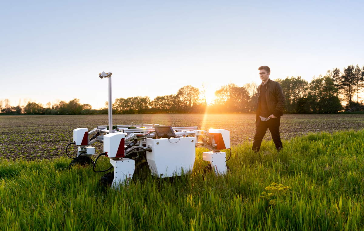 A mechanical engineer with sustainable agricultural robot in field